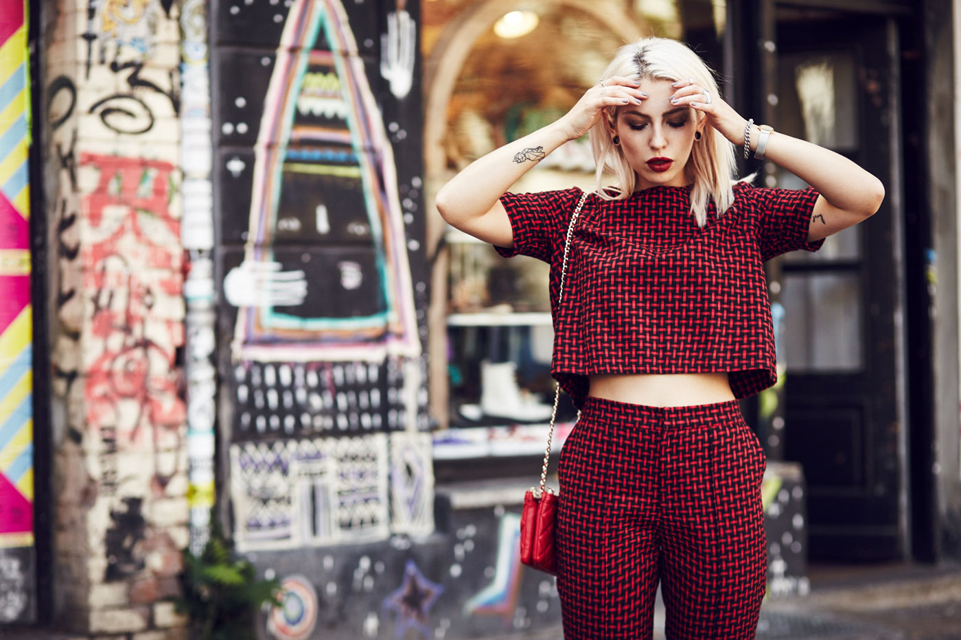 Masha Sedgwick, fashion blogger from Berlin is wearing a red two piece combined with a red Moschino bag and black loafers | Outfit