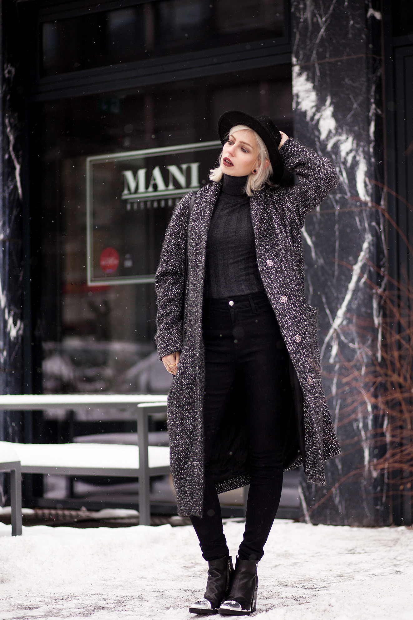 view more details on my blog   wearing black boots with a star from Love Moschino, an oversized wool coat from Marimekko, a black bag from Saint Laurent and a black jeans from AG   black, edgy, winter fashion   street style taken in Berlin   snow