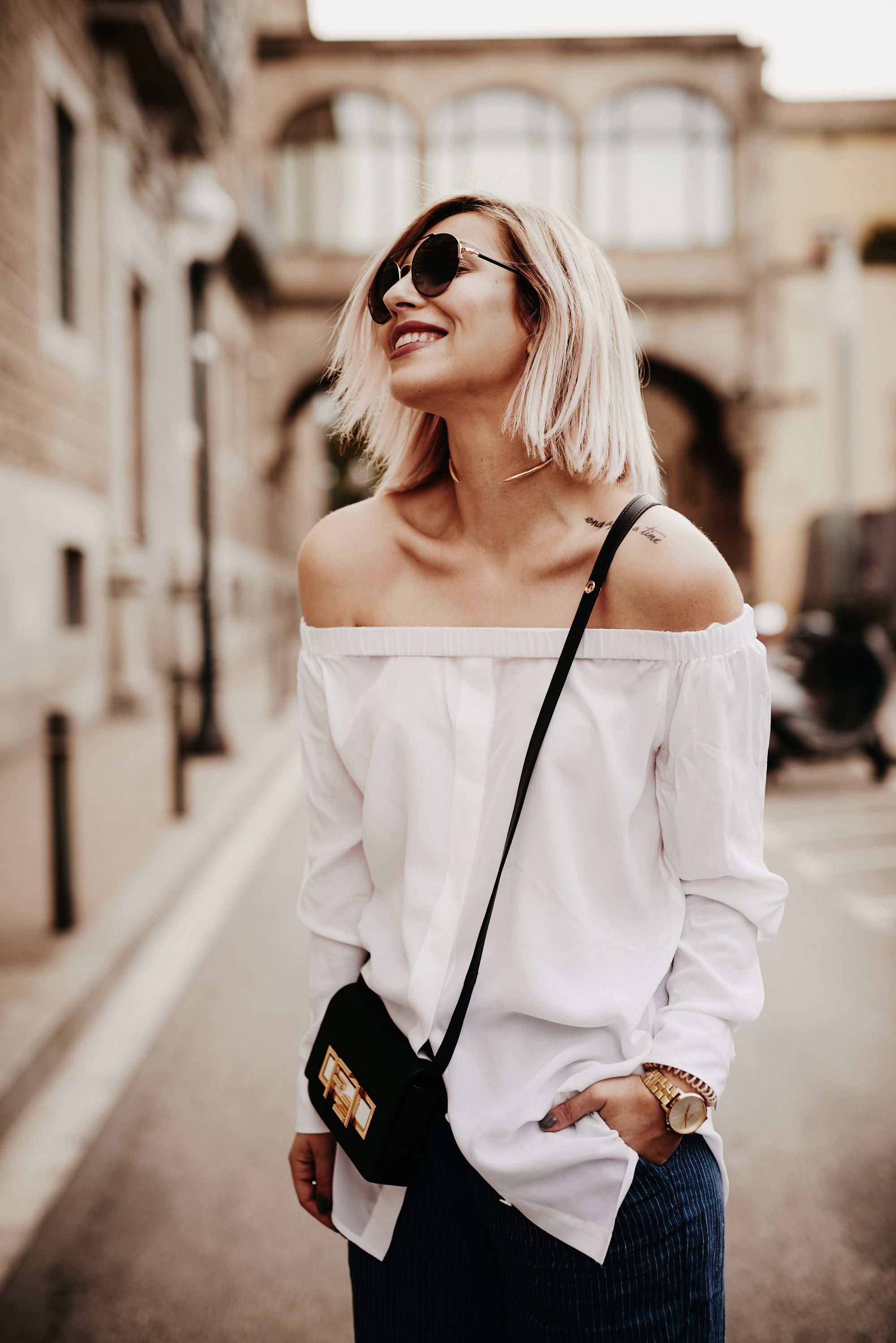 Outfit shooting in Barcelona   casual style wearing: off-shoulder shirt, Mom Jeans, Fendi 3Baguette and edgy heels   fashion blogger