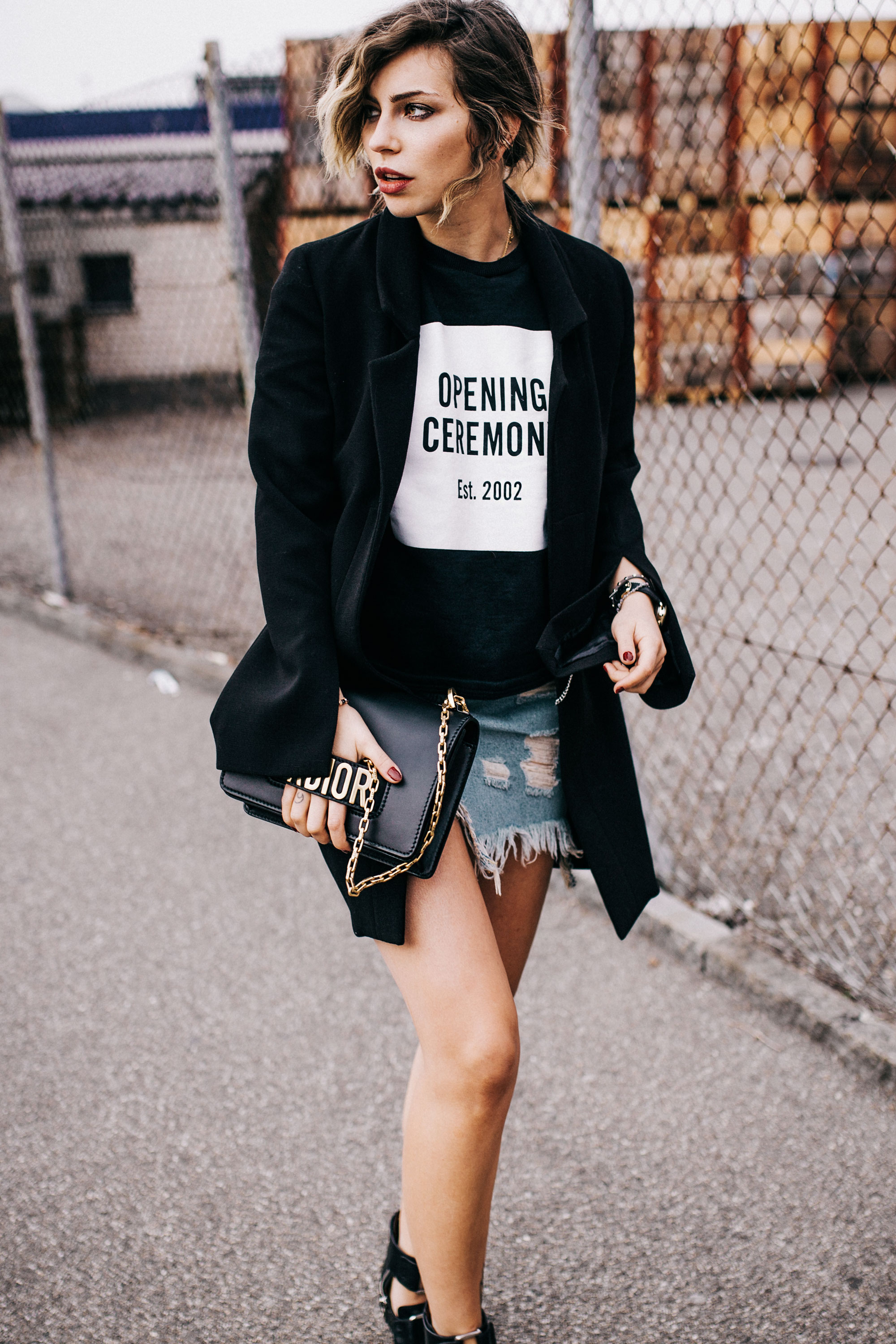 Fashion Editorial shooting with street art | style: rock, edgy, grunge, summer, dark, black, cool, industrial | wearing a Zara denim skirt, an oversized black blazer, cut out boots from 3.1. phillip Lim and an opening ceremony sweater tee