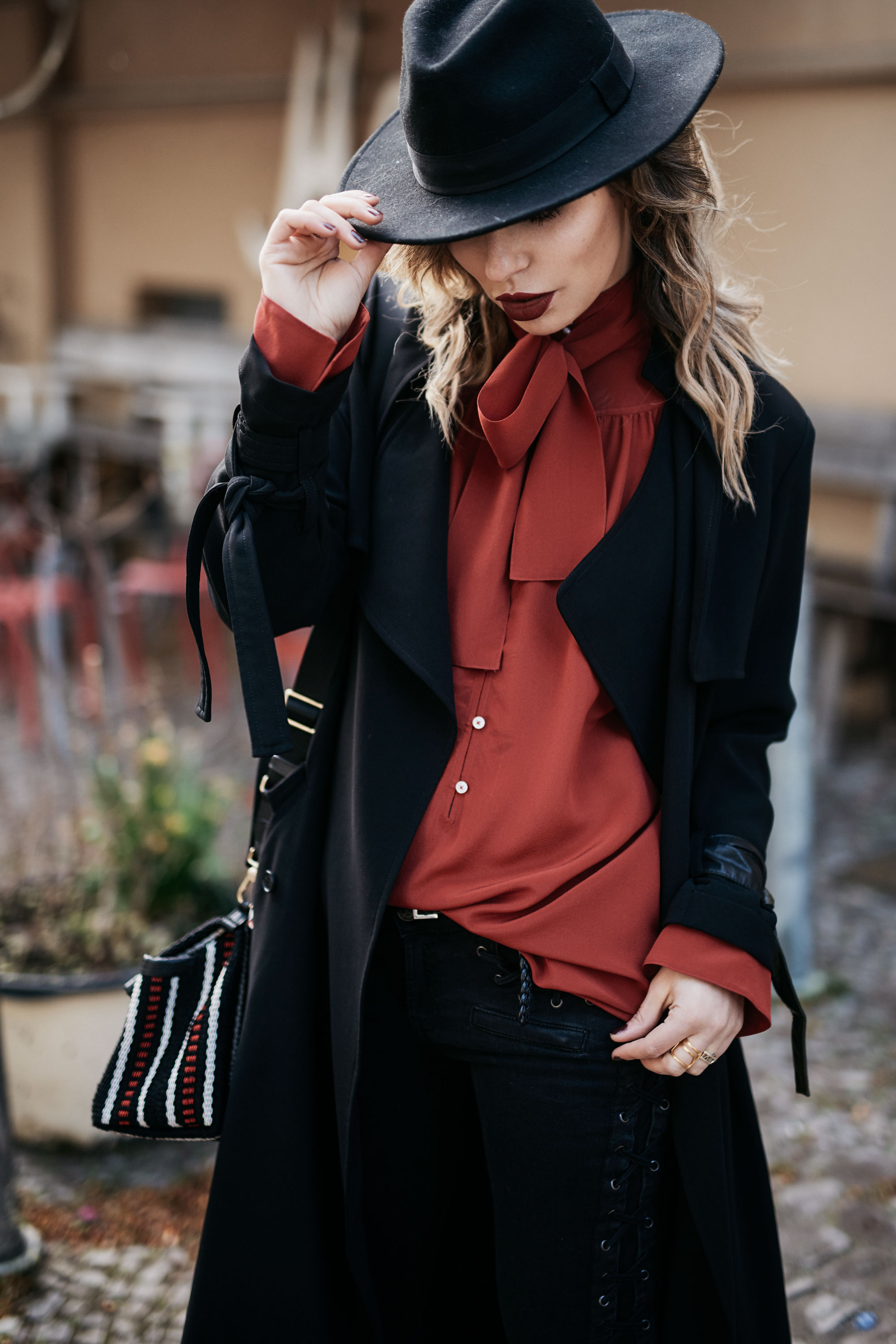 Designer Summer Sale | outfit: edgy, dark, sexy, classy, feminine | wearing a long black trench coat, laced up black jeans, red bow tie blouse