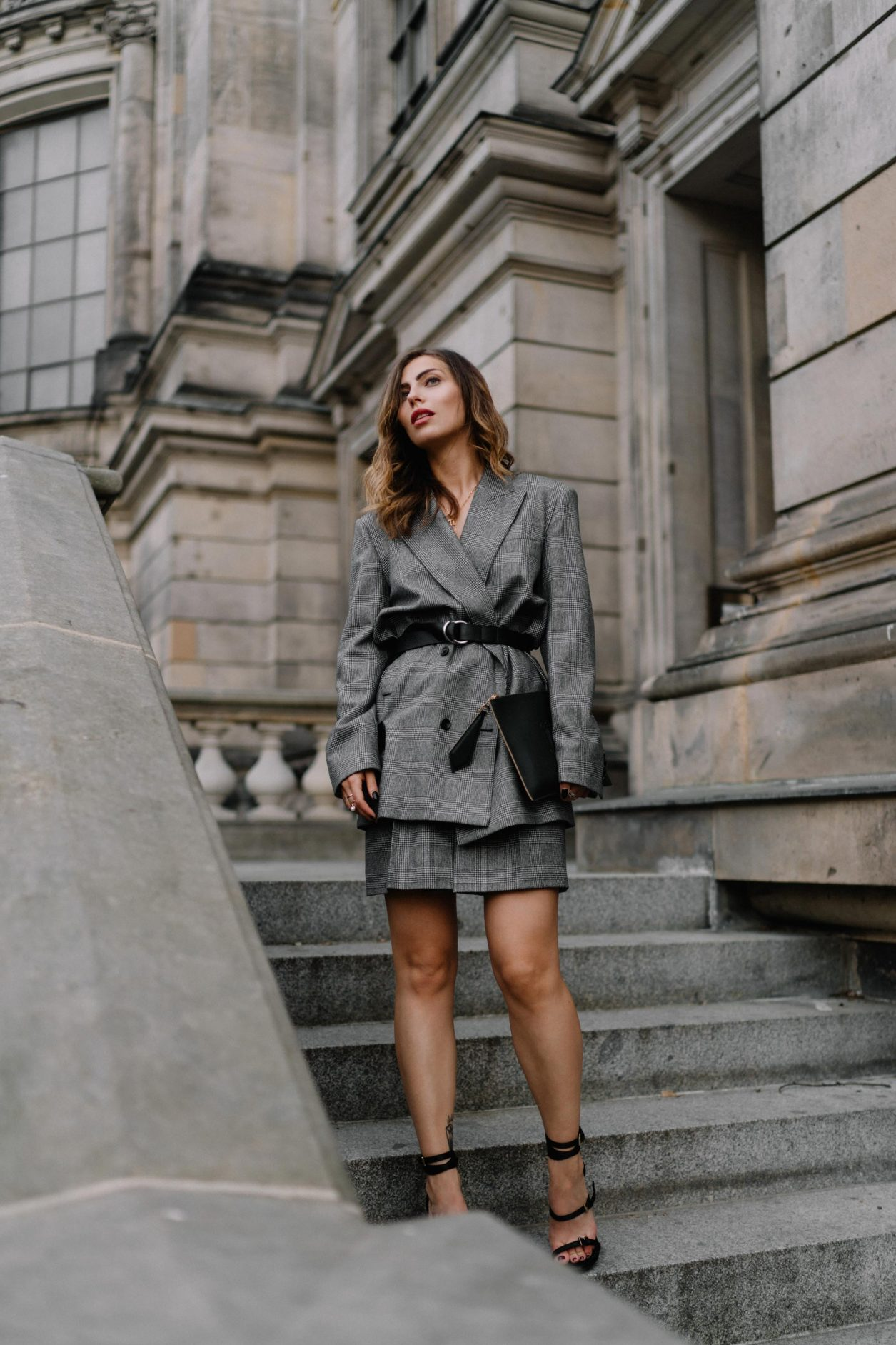 Business look by Max Mara: wearing grey checked crepe suit and mini skirt by Max Mara SS20, black leather envelope clutch by Max Mara, Nappa leather sandals Sylvia by Max Mara new collection, fine jewelry by Thomas Sabo, Georg Jensen, Close, Louis Vuitton; location: Berlin Museum Island, Berliner Dom, Berlin Fashion Blogger