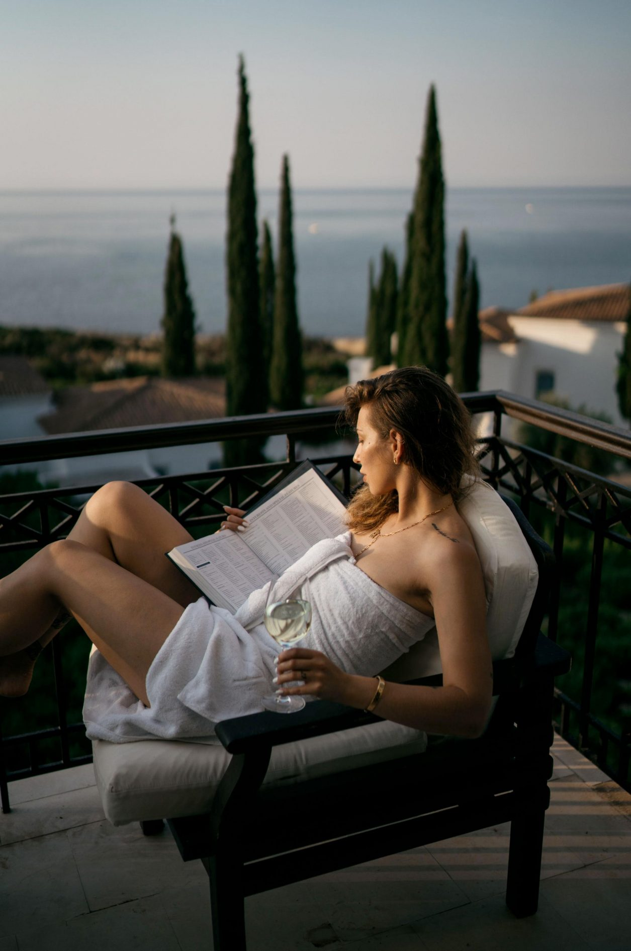 Anassa Resort - Luxury Spa Hotel in Cyprus, Greece. Balcony view, woman reading book and drinking wine