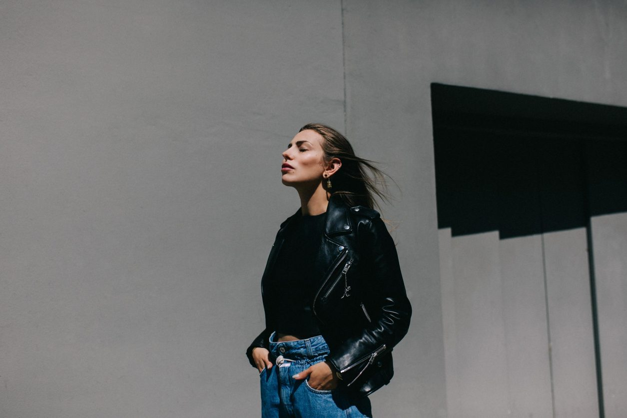 Fashion Editorial in the sun | Light Aesthetic | black leather jacket & blue paperbag jeans | neutral & minimalistic | concrete wall