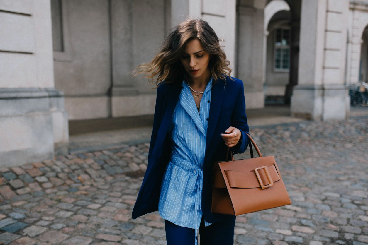 Street style by Masha Sedgwick wearing Lala Berlin at the Copenhagen Fashion Week SS20, blue Lala Berlin suit, brown BOYY bag, stripped blue Lala Berlin asymmetric blouse, Bally loafer