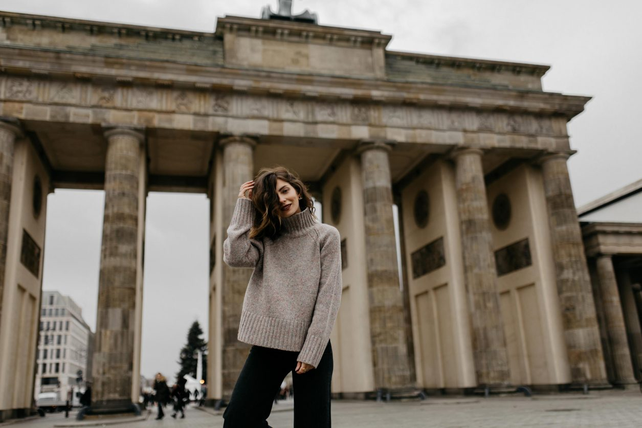 Streetstyle by Masha Sedgwick | AW 19 outfit: brown knit Closed, black wide cord pants from , black leather boots Filippa K | Berlin sightseeing photo spot: Brandenburger Tor