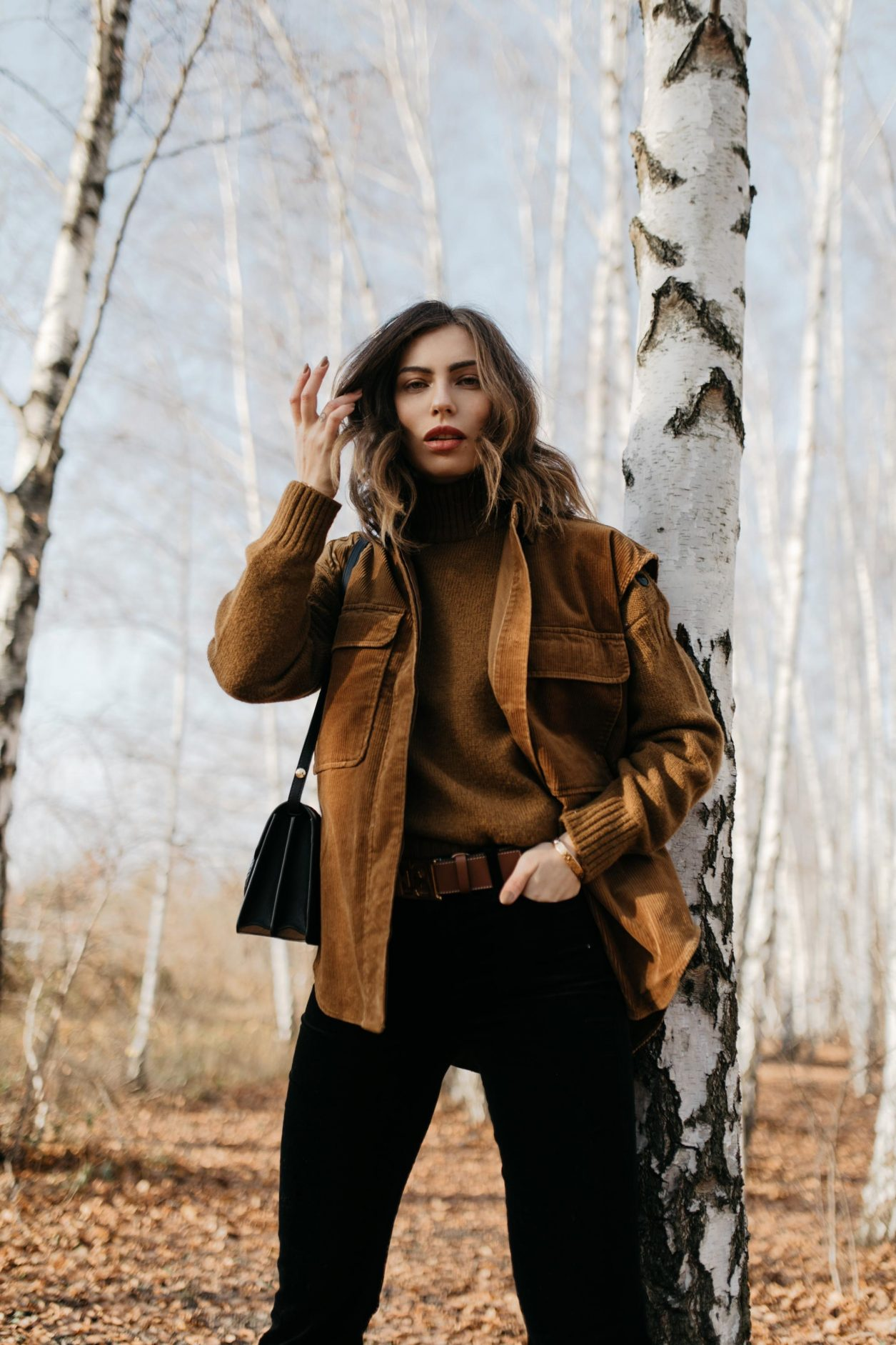Streetstyle editorial by Masha Sedgwick | Fall winter country style outfit, wearing  tobacco Closed pullover, tobacco cord west by Closed, bootcut jeans by J Brand, brown Escada belt, black black leather cross body bag By Malene Birger | Berlin photo spot: birch park