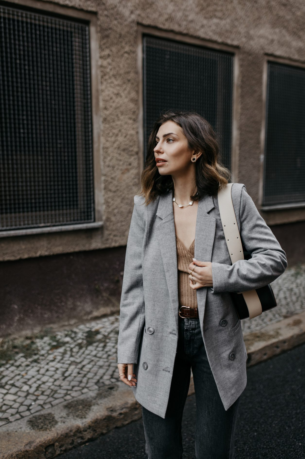 Streetstyle by Masha Sedgwick | Early spring city outfit inspiration, wearing beige classic Closed coat, beige-brown-black Yuzefi shoulder bag, grey Closed jeans, black &other Stories loafer with zipper, grey socks, grey Gestuz blazer, wrapped brown Baum & Pferdgarten shirt | Berlin street style editorial shooting