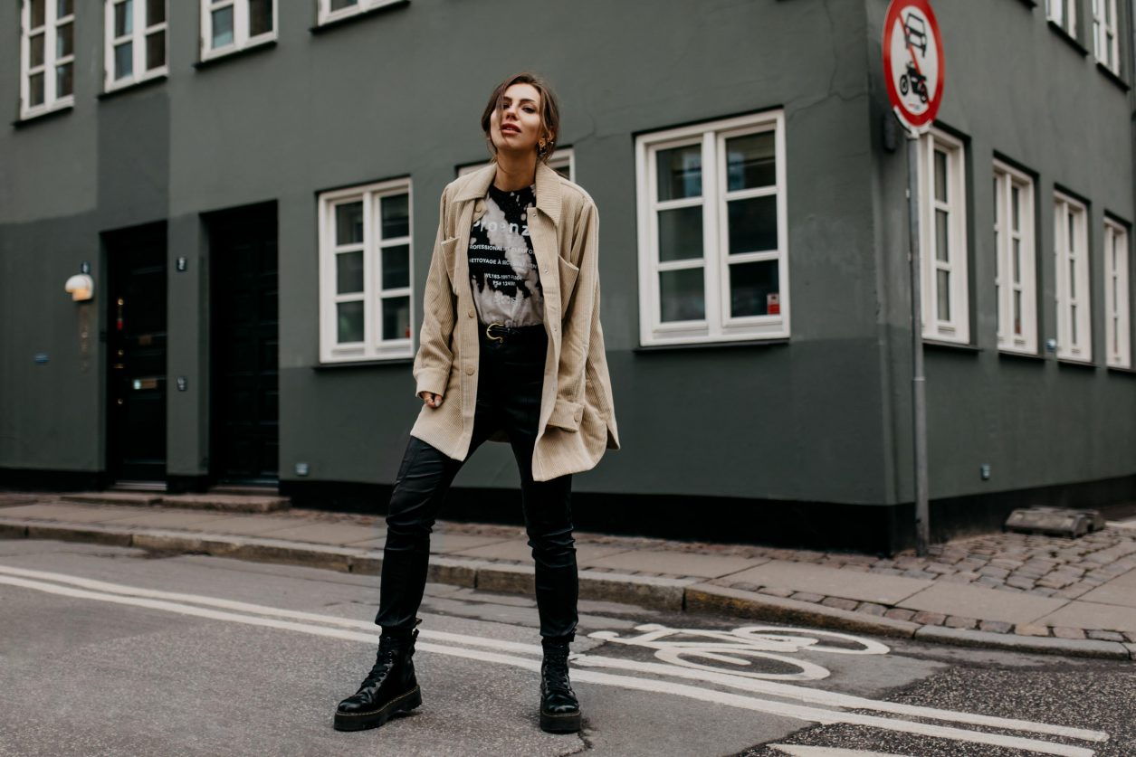 Copenhagen Fashion Week Streetstyle by Masha Sedgwick | Fashion and beauty blogger | Minimalistic Scandinavian style, everyday outfit ideas, casual feminine look: wearing black white long sleeve by Proenza Schouler, beige corduroy shirt by Second Female, black leather pants by H&M, black leather Boots by Dr. Martens, minimalistic fine jewelry Face Earring by Persee, pearl ear cuffs: Maria Black | Photo spot: Copenhagen city