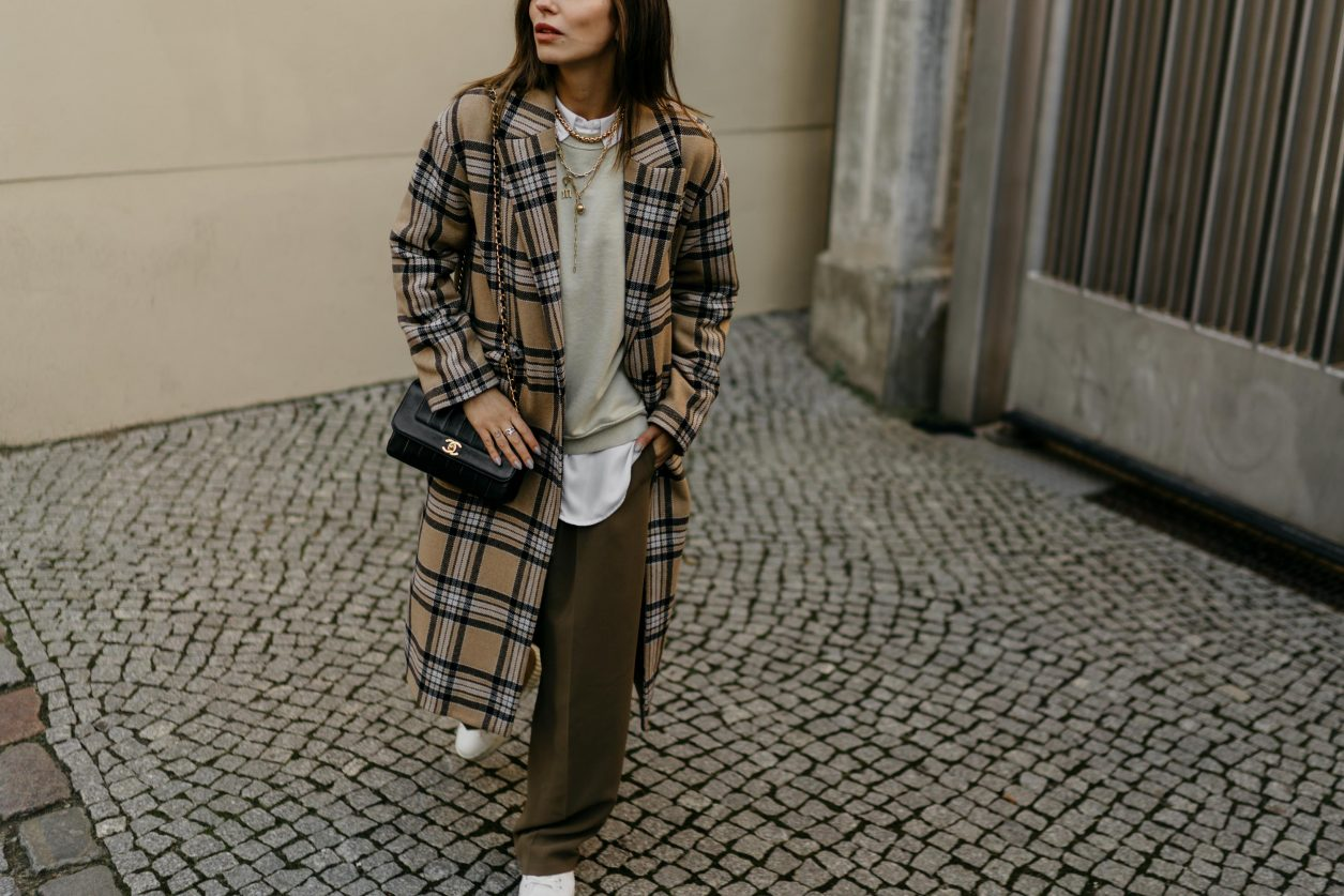 Streetstyle by Masha Sedgwick | Fashion and beauty blogger from Berlin, Germany | Everyday outfit inspiration, feminine casual ootd, cozy spring outfit | Wearing SET fashion beige black checked wool coat, sage green oversized sweatshirt by Topshop, brown wide jogging pants by Topshop, white oversized blouse by SET fashion, white leather Diesel sneaker, black vintage Chanel shoulder bag, golden necklaces