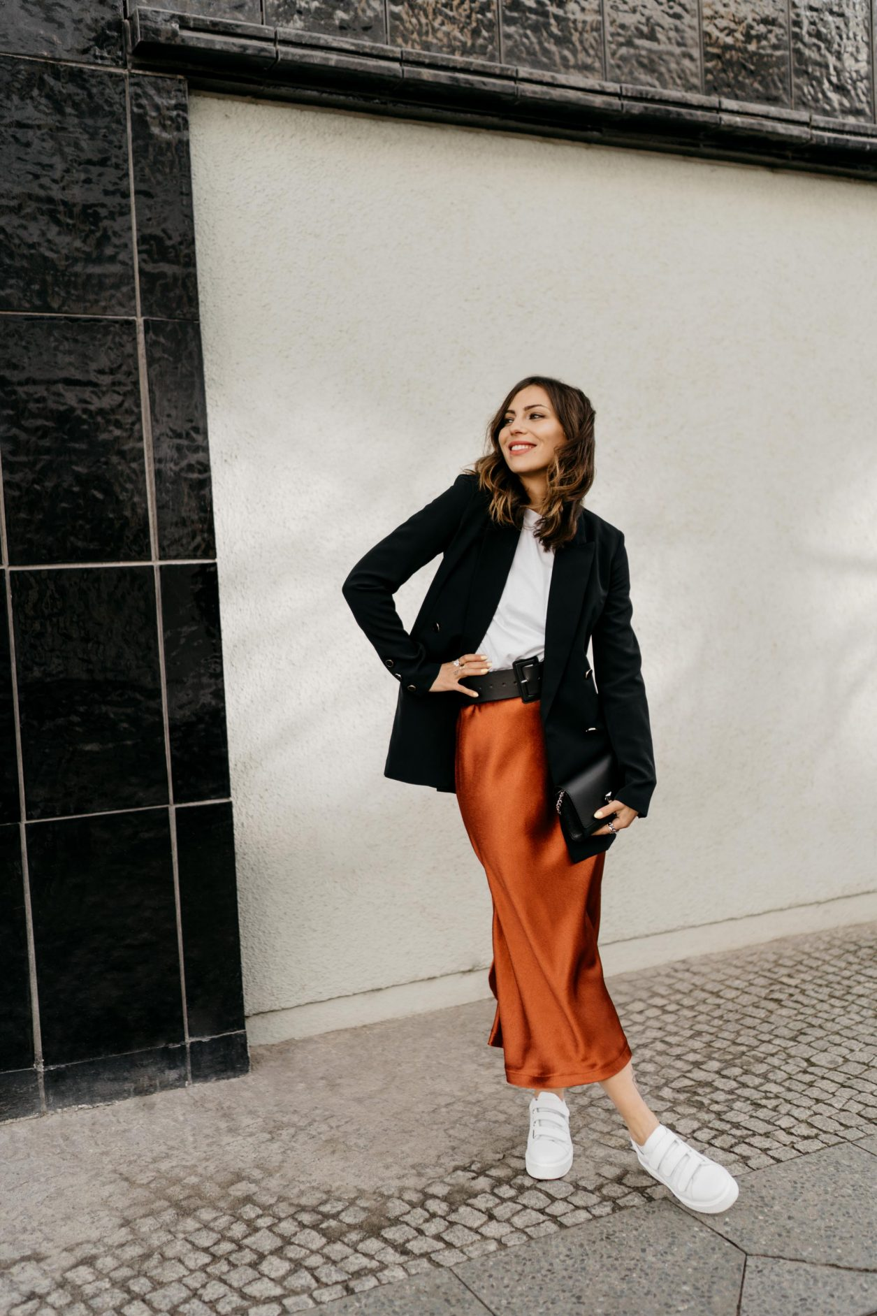 Spring Streetstyle Outfit by Masha Sedgwick   Fashion Blogger from Berlin, Germany   Wearing black Guess blazer, orange red satin Closed midi skirt, black leather belt by Gina Tricot, Calvin Klein Jeans basic white shirt with logo on the pocket, black belt leather BOSS bag, white sneaker by Zign   how to style white sneaker in a business outfit