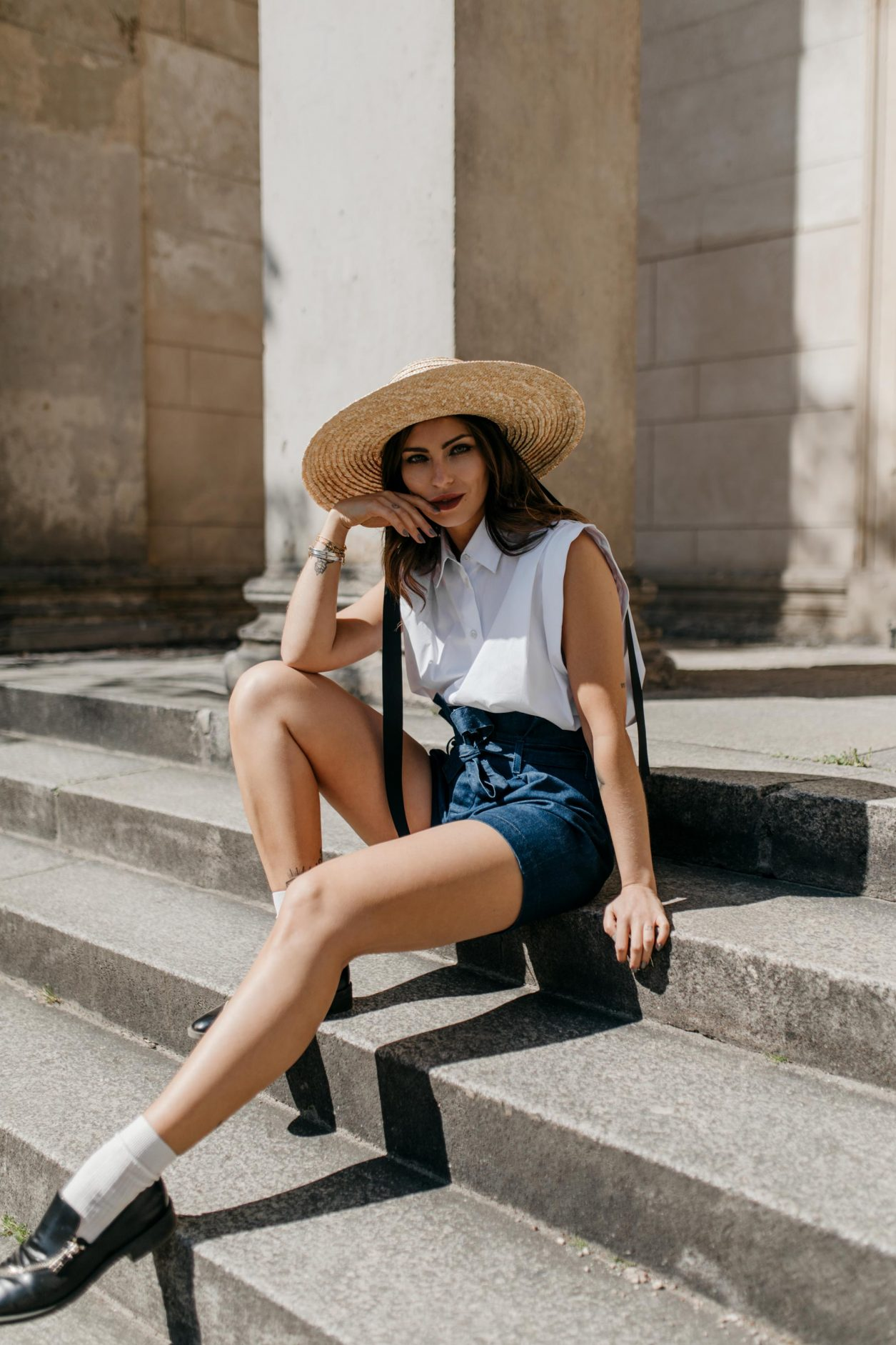 Anzeige | Streetstyle by Masha Sedgwick | Fashion blogger from Berlin, Germany | Spring summer outfit inspiration, minimalistic, english style, effortless cool | Wearing paperbag shorts and sleeveless white blouse by 7 for all mankind, vintage short Burberry coat, straw hat, white socks with black leather loafers