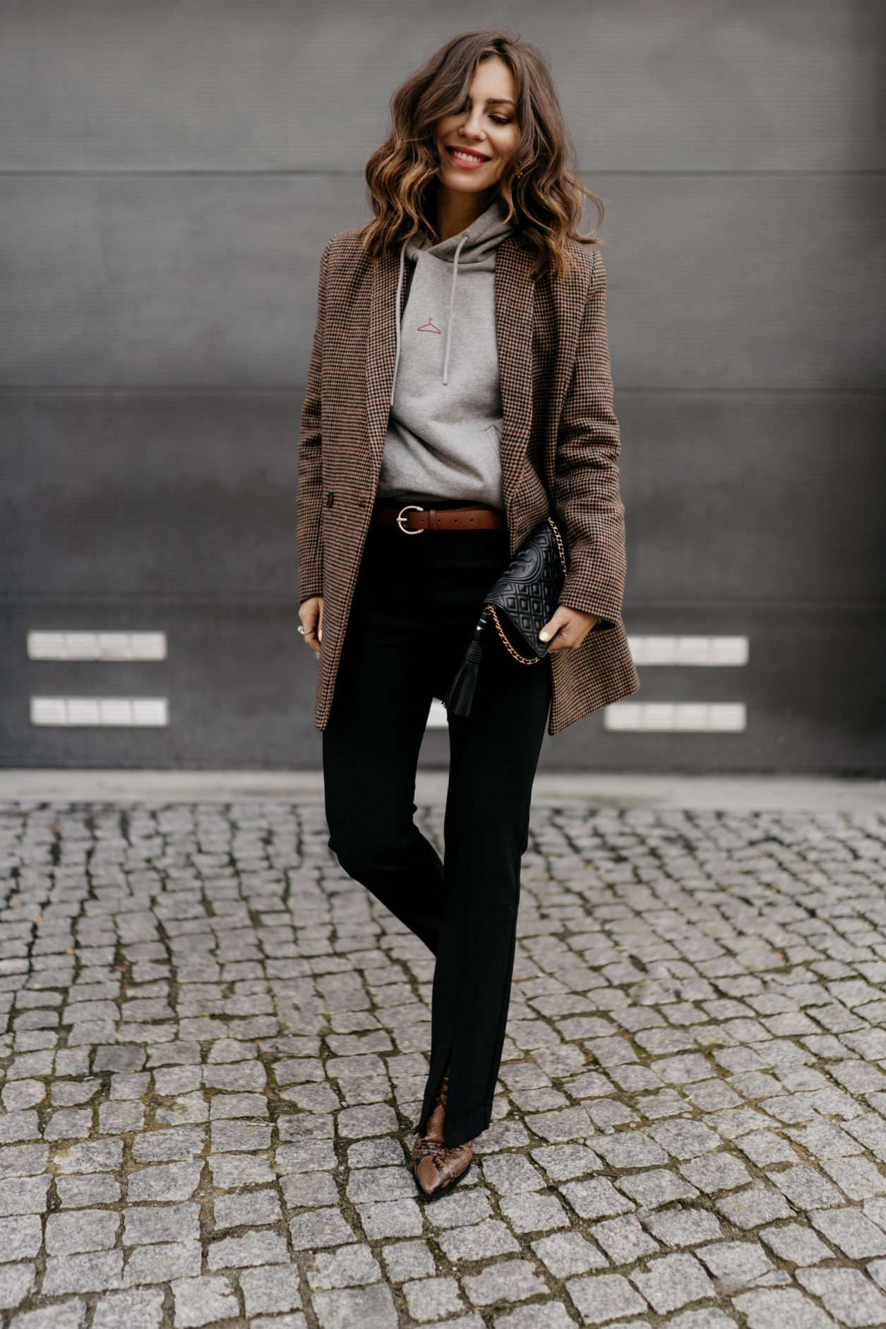 Streetstyle by Masha Sedgwick | Fashion blogger from Berlin, Germany | Everyday business casual outfit inspiration, wearing brown checked Samsoe Samsoe blazer, light grey logo Holzweiler hoodie, brown leather Zign belt, front splits black tailored pants by Samsoe Samsoe, brown sneak leather open boots by Zign, Tory Burch shoulder mini bag