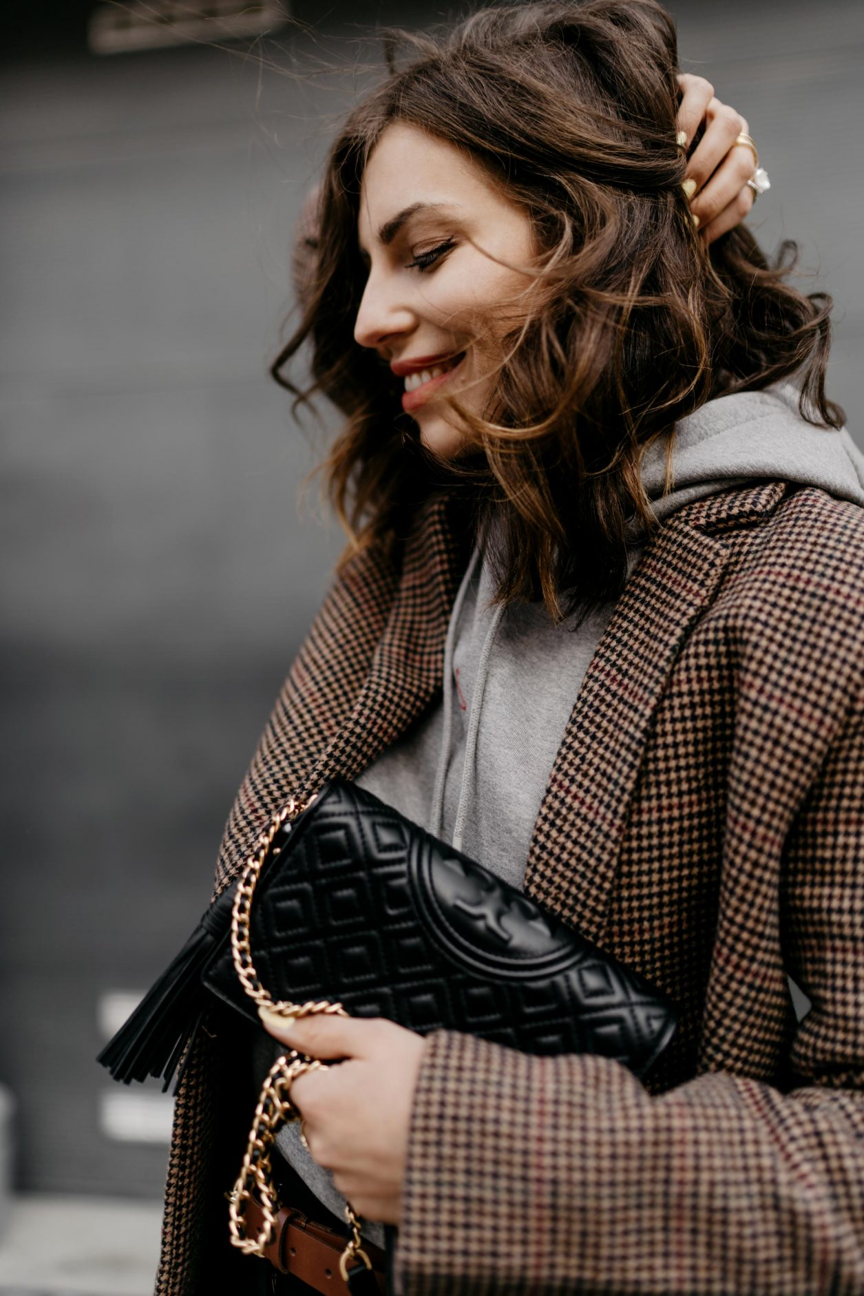 Streetstyle portrait by Masha Sedgwick | Fashion blogger from Berlin, Germany | Everyday business casual outfit inspiration, wearing brown checked Samsoe Samsoe blazer, light grey logo Holzweiler hoodie, brown leather Zign belt, Tory Burch shoulder mini bag