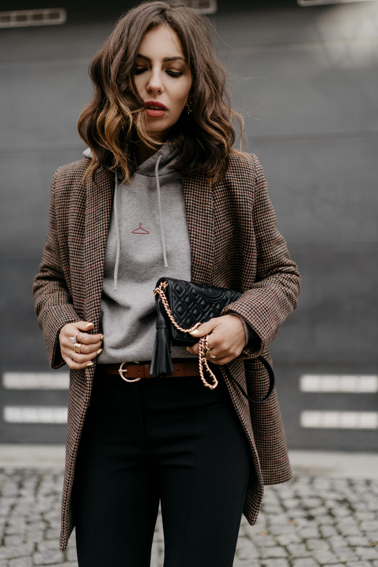 Streetstyle by Masha Sedgwick | Fashion blogger from Berlin, Germany | Everyday business casual outfit inspiration, wearing brown checked Samsoe Samsoe blazer, light grey logo Holzweiler hoodie, brown leather Zign belt, front splits black tailored pants by Samsoe Samsoe, Tory Burch shoulder mini bag
