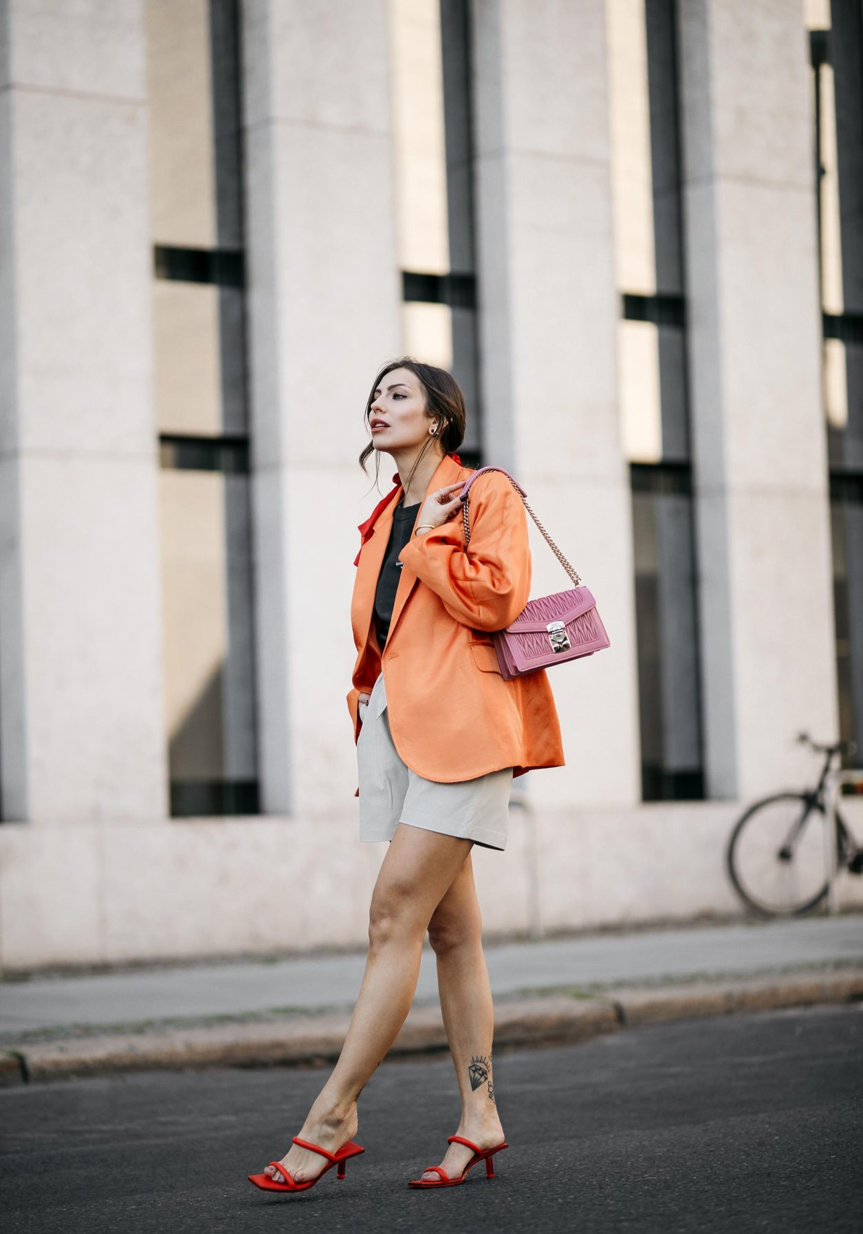 Summer Streetstyle Look by Masha Sedgwick | Photographer: Jeremy Moeller | Summer style trends & outfit inspiration, fashion blogger from Berlin, Germany | Wearing orange Baum Pferdgarten Blazer, graphic grey Acne Studios logo shirt, white leather Copenhagen Muse paperboy shorts, pink Miu Miu shoulder bag, red straps sandals by Charles & Keith | Hair style: messy ponytail
