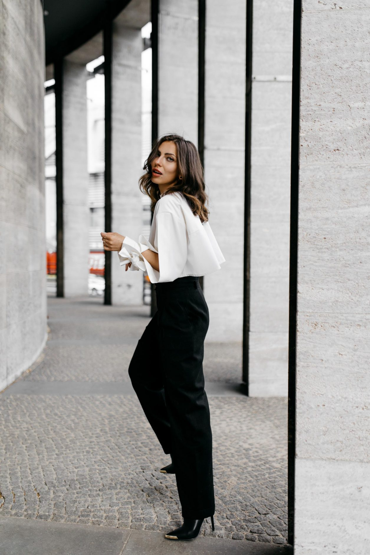 Anzeige | Streetstyle by Masha Sedgwick - fashion and beauty blogger from Berlin, Germany | Photographer Tonya Matyu | Minimalistic black and white outfit, business chic, high end, wearing black vintage Chanel wool pants, white cropped Nobi Talai blouse with puffed arms, dark day make-up, black leather high heels | Photo spot: Berlin Messe ICC