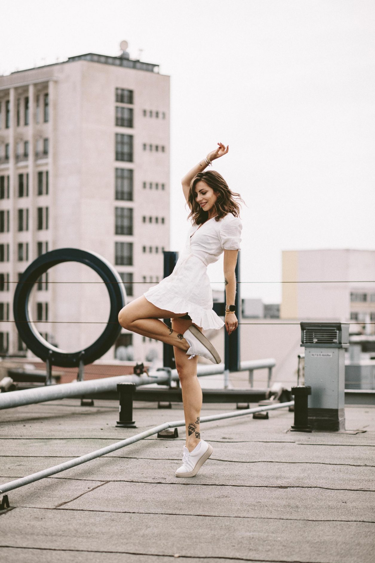 Anzeige   Fashion and beauty blogger from Berlin, Germany - Masha Sedgwick on the roof of Hotel Zoo, summer outfit inspiration: cute white linen wrapped mini dress, golden jewelry from Ariane Ernst, Thomas Sabo, Bulgari ring, white Coach sneaker   Inked fashion blogger, minimalistic, chic, effortless cool, streetstyle inspiration, ootd, photographer Tonya Matyu