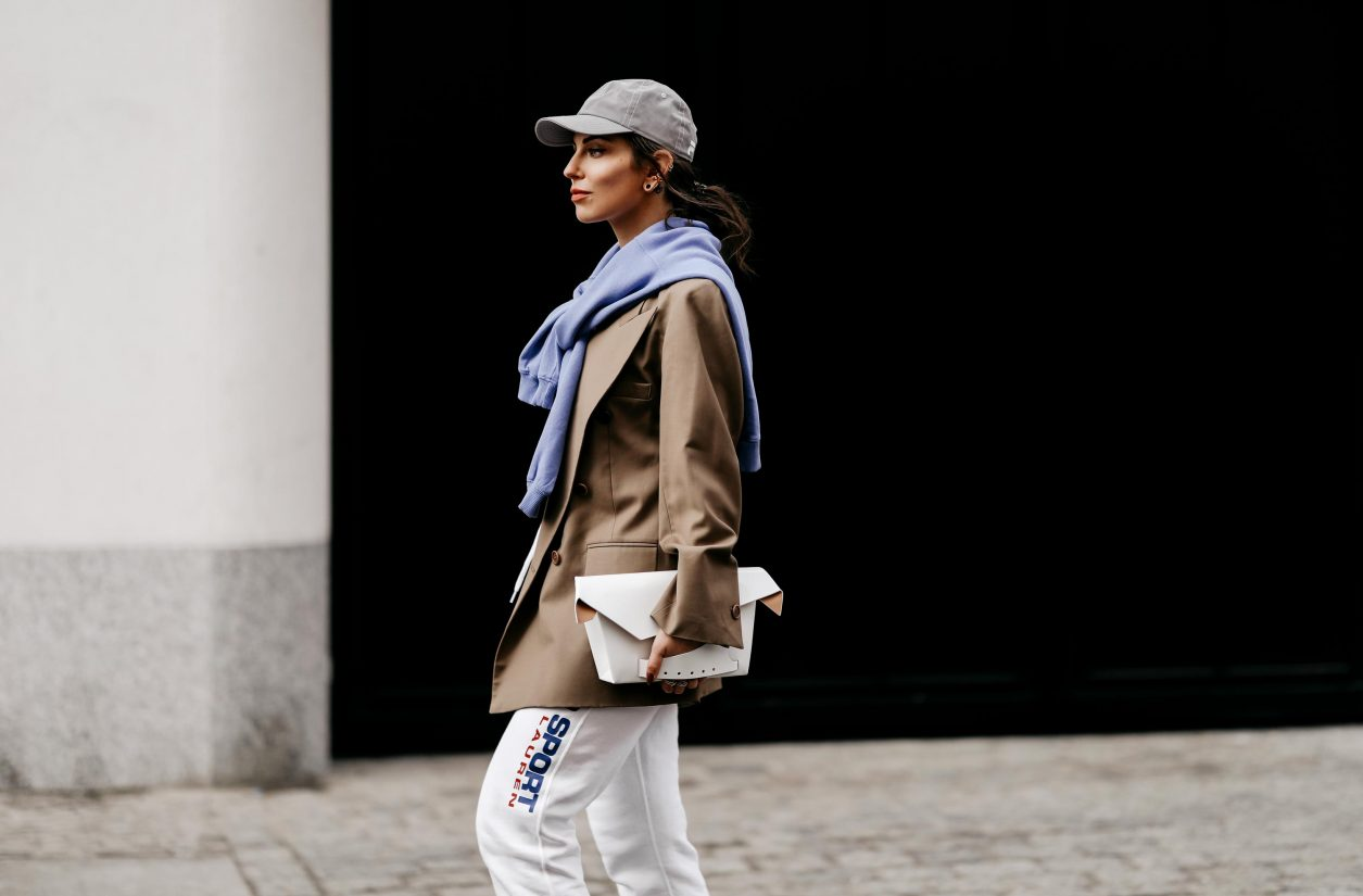 Fashion blogger from Berlin, Germany wearing white jogging Polo Ralph Lauren pants, beige Envelope1976 blazer, lilac sweatshirt, grey Film basecap, white t-shirt, white lack leather Maison Margiela clutch, grey Converse chucks | Spring summer 2021 Streetstyle outfit inspiration, SS fashion trends | photographer Jeremy Moeller