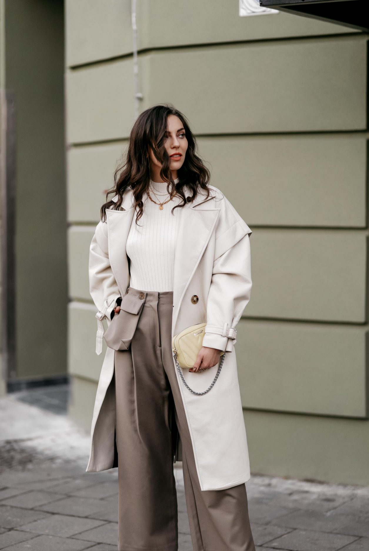 Spring Streetstyle outfit by Berlin fashion blogger Masha Sedgwick | Minimalistic, effortless cool, casual chic, wearing off white lack leather Apparis trench coat, off white Iris & Ink knit shirt, brown wide Frankie Shop pants with front pocket, lemon yellow WEAT crossbody mini bag, golden rings and necklaces, khaki green Charles & Keith pumps, hair style: black waves, photographer Jeremy Moeller
