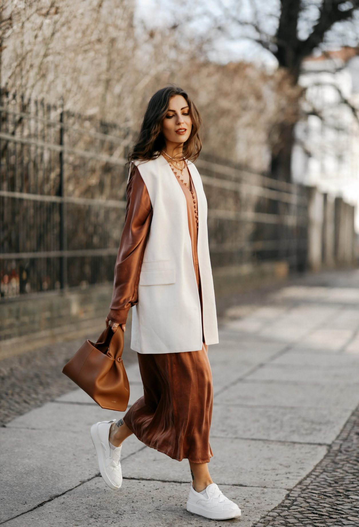 Streetstyle by Masha Sedgwick wearing bronze brown silk buttoned maxi dress by Envelope1976, white Zara blazer west, white slip-on Copenhagen studios sneaker, brown Polene Paris bag | Spring dress styling idea