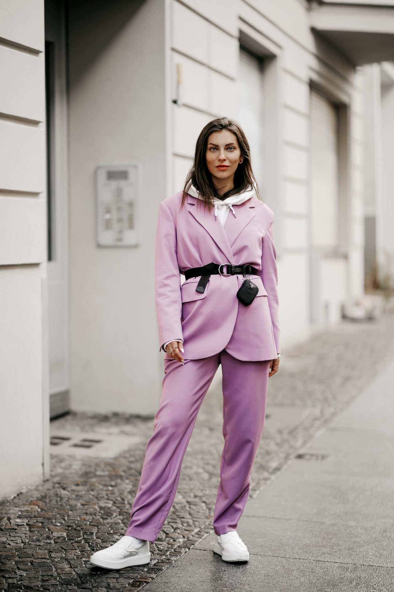 Streetstyle outfit by fashion blogger from Berlin, Germany | Minimalistic everyday outfit, business casual, spring suit ideas, spring colors, ss21 wardrobe must-haves, wearing lilac Market suit, Prada belt with belt-bag, white nail polish, white leather loafer, white hoodie